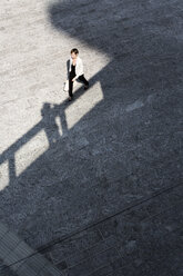 Businesswoman crossing square, seen from bove - GIOF04020