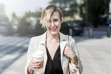 Portrait of smiling businesswoman with Coffee to go - GIOF04023