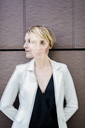 Blond businesswoman leaning against wall, dopple exposure - GIOF04026