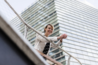 Smiling businesswoman leaning on railing - GIOF04029