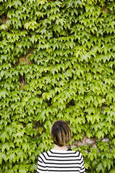 Back view of woman in front of facade greenery - GIOF04038