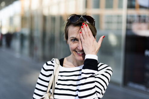 Portrait of smiling woman covering eye with her hand - GIOF04041