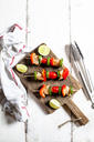 Grill skewers with raw chicken, tomato, bell pepper and zucchini on chopping board - SBDF03707