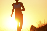 Silhouette of young woman running at sunset - ISF18584