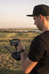 Man holding remote control for a drone in a field - ACPF00147