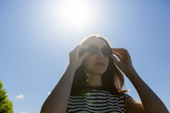 Portrait of young woman at backlight wearing sunglasses - GIOF04046