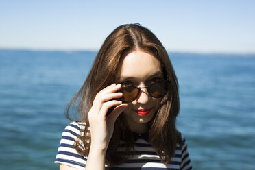 Italy, Lake Garda, portrait of smiling young woman with sunglasses - GIOF04049
