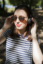 Portrait of smiling young woman wearing sunglasses listening music with headphones - GIOF04052