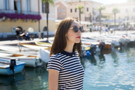 Italy, Bardolino, Lake Garda, portrait of young woman wearing sunglasses - GIOF04055