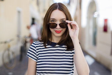 Italy, Bardolino, portrait of smiling young woman with sunglasses - GIOF04058