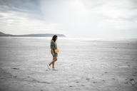 South Africa, Western Cape, Noordhoek, woman walking on the beach - DAWF00674