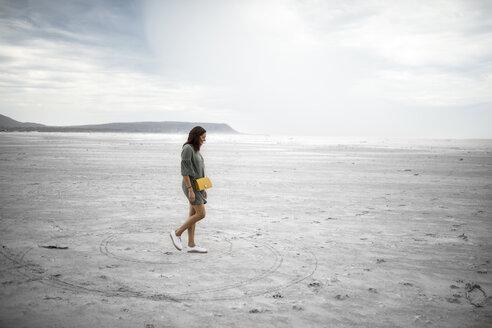 South Africa, Western Cape, Noordhoek, woman walking on the beach - DAWF00674