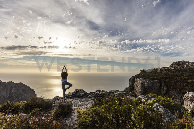 South Africa, Cape Town, Table Mountain, woman doing yoga on a rock at sunset - DAWF00683 - Daniel Waschnig Photography/Westend61