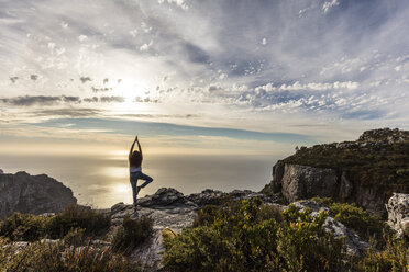 South Africa, Cape Town, Table Mountain, woman doing yoga on a rock at sunset - DAWF00683