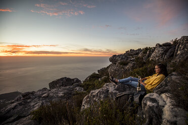 South Africa, Cape Town, Table Mountain, woman sitting on a rock drinking wine at sunset - DAWF00686