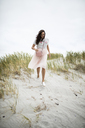 South Africa, Western Cape, Hermanus, happy woman walking in beach dune - DAWF00689
