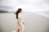 South Africa, Western Cape, Hermanus, woman holding hand on the beach - DAWF00692