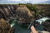 Zimbabwe, legs of a man resting at Victoria Falls - DAWF00698