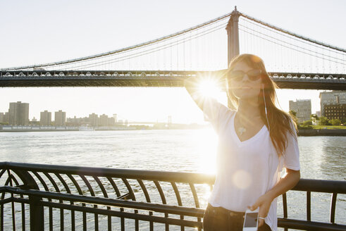 Young woman in sunlight with Manhattan Bridge, Brooklyn, USA - ISF18595