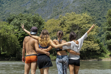 Laos, group of friends standing at a river embracing - AFVF01151