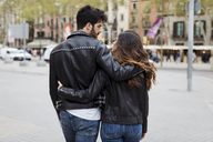 Spain, Barcelona, young couple embracing and walking in the city - MAUF01545