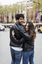 Spain, Barcelona, young couple embracing and walking in the city - MAUF01548