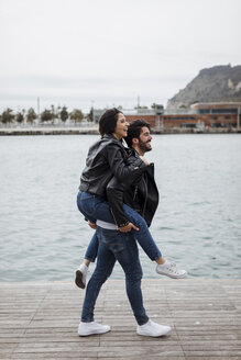 Spain, Barcelona, happy young couple having fun at the coast - MAUF01551