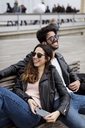 Spain, Barcelona, happy young couple with cell phone resting on a bench - MAUF01557