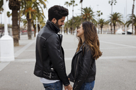 Spain, Barcelona, smiling young couple on promenade with palms - MAUF01560