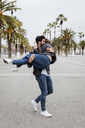 Spain, Barcelona, happy young man carrying girlfriend on promenade with palms - MAUF01563