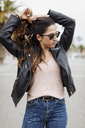 Spain, Barcelona, young woman wearing leather jacket doing her hair - MAUF01569