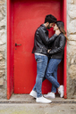 Affectionate young couple kissing at red door - MAUF01578
