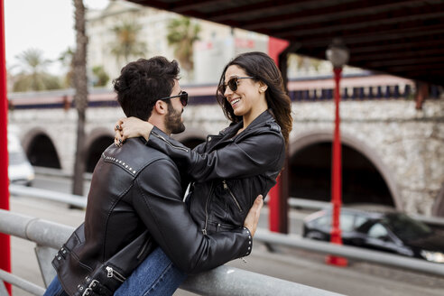Spain, Barcelona, happy young couple embracing in the city - MAUF01587