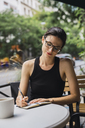 Young woman sitting in coffee shop, brainstorming, writing notes in notebook - KKAF01259
