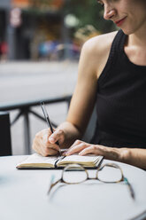 Young woman sitting in coffee shop, brainstorming, writing notes in notebook - KKAF01262