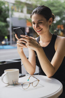 Young woman sitting in cofee shop, using smartphone - KKAF01268