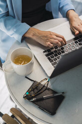 Young businesswoman sitting in coffee shop, using laptop - KKAF01271