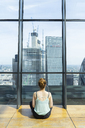 UK, London, back view of young woman looking at skyscrapers of financial district - AFV01157