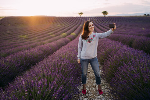 France, Valensole, smiling woman taking selfie at lavender field by sunset - GEMF02223