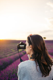 France, Valensole, woman taking photos with camera in front of lavender field at sunset - GEMF02235