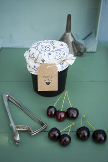 Glass of homemade cherry jam, cherries and pit remover - GISF00343
