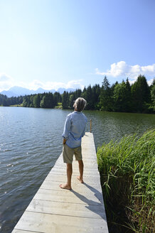 Germany, Mittenwald, back view of mature man standing barefoot on jetty at lake relaxing - ECPF00237