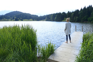 Germany, Mittenwald, woman standing on jetty at lake looking at distance - ECPF00246
