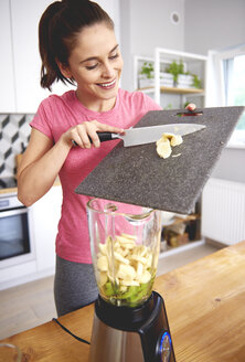 Smiling young woman preparing smoothie in the kitchen - ABIF00780