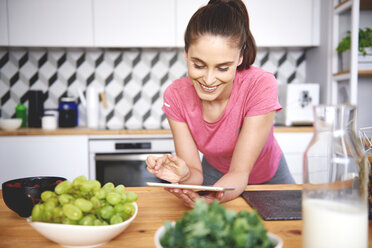 Smiling young woman using tablet in the kitchen - ABIF00783