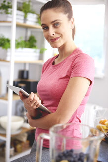 Portrait of smiling young woman with tablet in the kitchen - ABIF00786