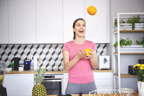 Portrait of young woman juggling with oranges in the kitchen - ABIF00789