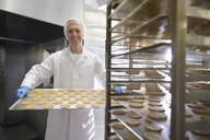 Portrait of baker holding tray of freshly baked biscuits in food factory - CUF43700