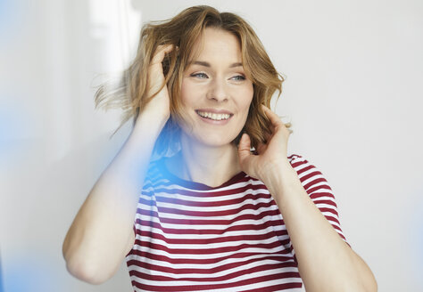 Portrait of smiling woman wearing red-white striped t-shirt - PNEF00775