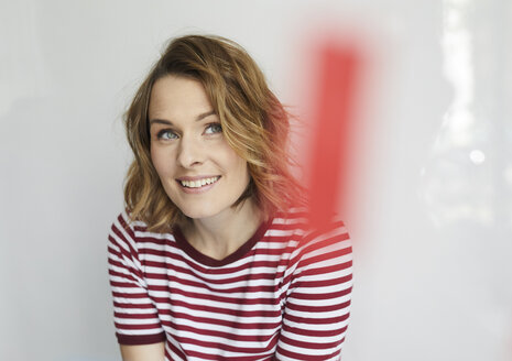 Portrait of smiling woman wearing red-white striped t-shirt - PNEF00784